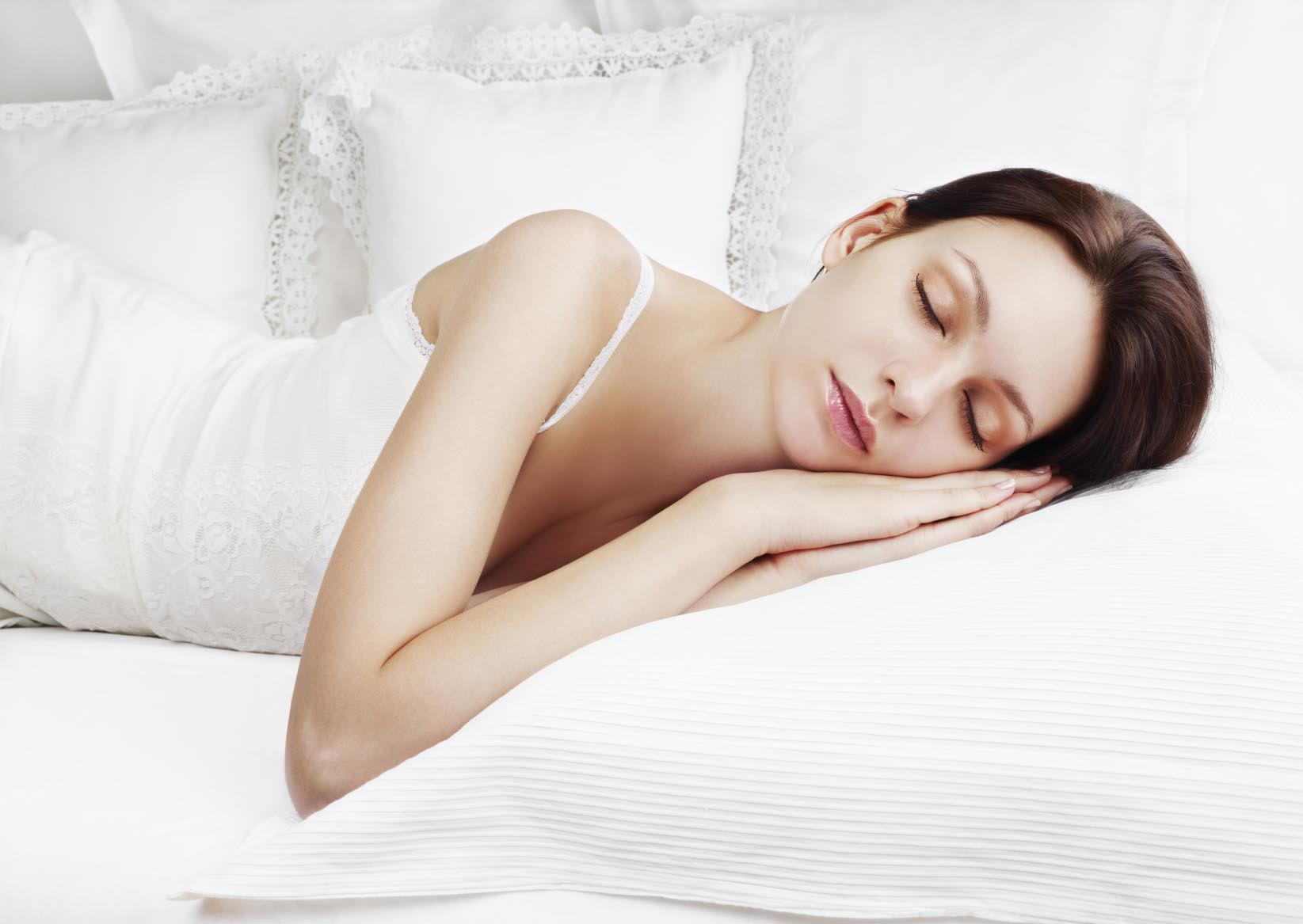 Beautiful woman sleeping on white bed linen